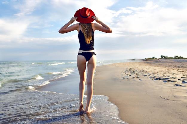 Jovem mulher loira posando de volta e andando sozinha perto do oceano, praia solitária, slim bode, vestindo biquíni preto e elegante chapéu vermelho, incrível vista da natureza, viajar na praia.