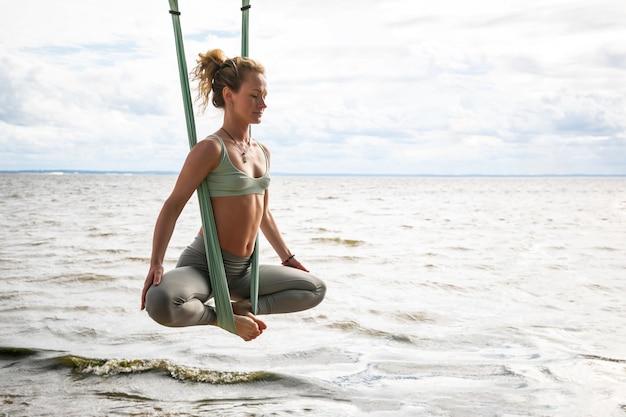 Jovem mulher loira praticando ioga aérea em rede de seda na praia. treinador profissional faz exercícios de alongamento em ioga voadora antigravitacional ao ar livre à beira-mar. bem-estar e conceito saudável.