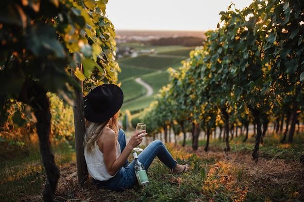 Jovem mulher loira relaxante nas vinhas na temporada de verão com uma garrafa de vinho