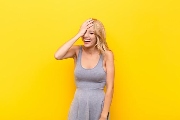 Jovem mulher loira rindo e batendo na testa