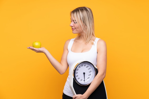 Jovem mulher loira russa sobre parede amarela isolada, segurando uma máquina de pesar enquanto olha uma maçã