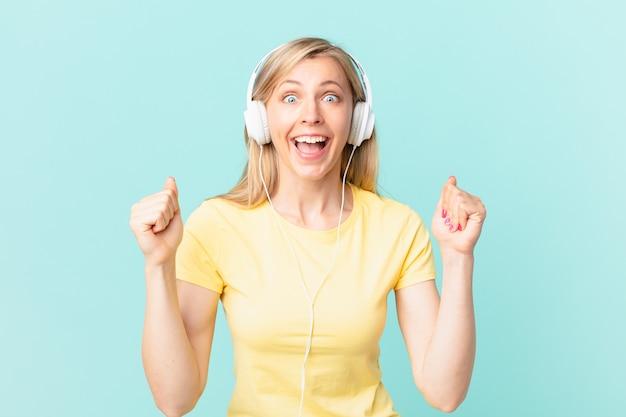 Jovem mulher loira se sentindo chocada, rindo e comemorando o sucesso e ouvindo música.