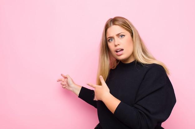 Jovem mulher loira se sentindo chocado e surpreso, apontando para copiar o espaço ao lado com olhar espantado, de boca aberta contra a parede plana