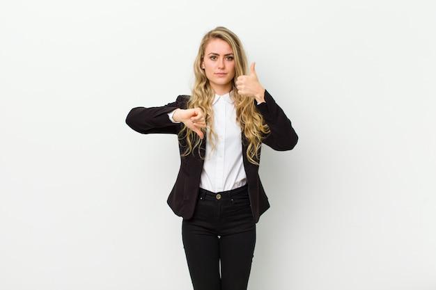 Jovem mulher loira se sentindo confusa, sem noção e insegura, ponderando o bem e o mal em diferentes opções ou escolhas contra a parede branca