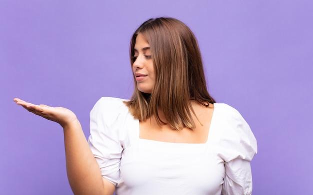 Jovem mulher loira se sentindo feliz e sorrindo casualmente, olhando para um objeto ou conceito seguro na mão ao lado