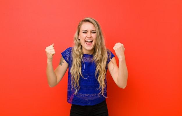 Jovem mulher loira se sentindo feliz, positivo e bem sucedido, comemorando a vitória, realizações ou boa sorte contra a parede vermelha