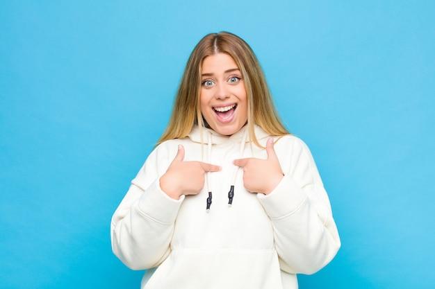 Jovem mulher loira se sentindo feliz, surpreso e orgulhoso, apontando para si mesmo com um olhar excitado e espantado por cima do muro