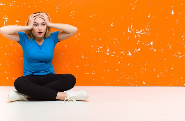 Jovem mulher loira se sentindo horrorizada e chocada, levantando as mãos à cabeça e entrando em pânico por um erro sentado no chão