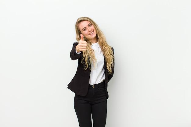 Jovem mulher loira se sentindo orgulhoso, despreocupado, confiante e feliz, sorrindo positivamente com os polegares para cima na parede branca
