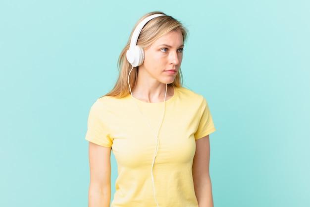 Jovem mulher loira se sentindo triste, chateada ou com raiva e olhando para o lado e ouvindo música.