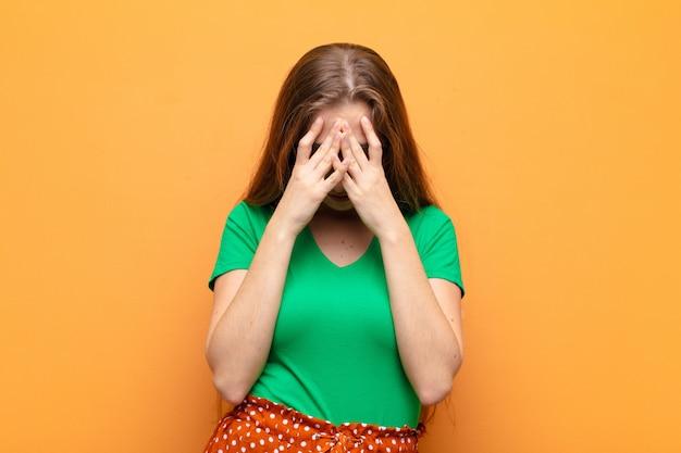 Jovem mulher loira se sentindo triste, frustrada, nervosa e deprimida, cobrindo o rosto com as duas mãos, chorando