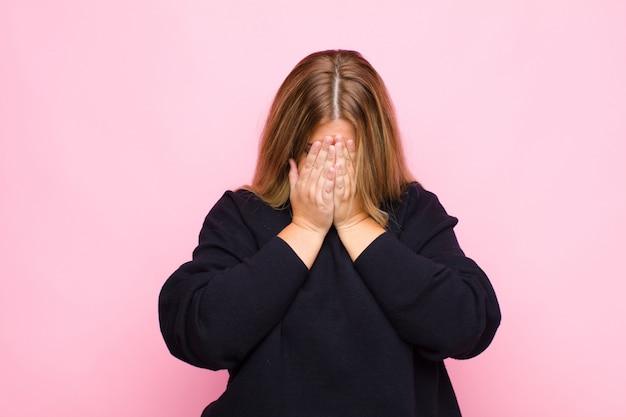 Jovem mulher loira se sentindo triste, frustrado, nervoso e deprimido, cobrindo o rosto com as duas mãos, chorando contra a parede plana