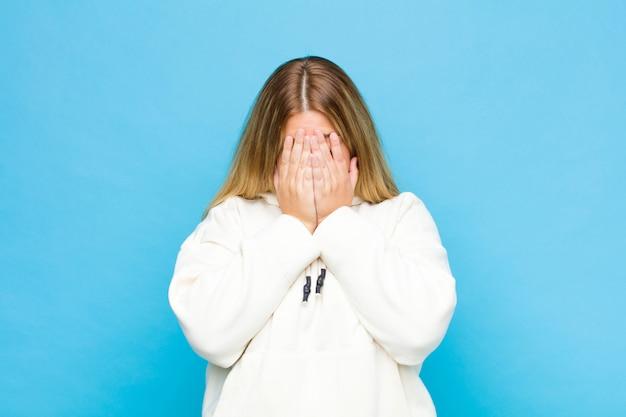 Jovem mulher loira se sentindo triste, frustrado, nervoso e deprimido, cobrindo o rosto com as duas mãos, chorando na parede plana