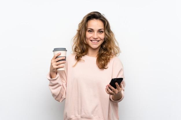 Jovem mulher loira segurando café para levar e um celular