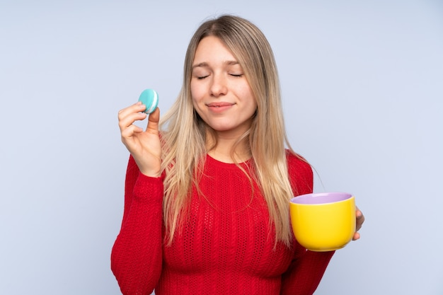 Jovem mulher loira segurando macarons franceses coloridos e um copo de leite
