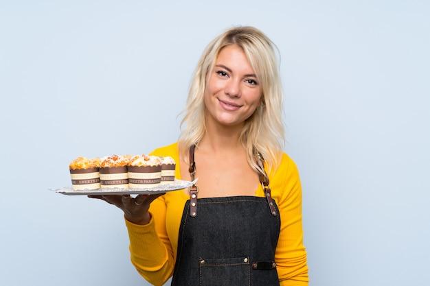 Jovem mulher loira segurando mini bolos