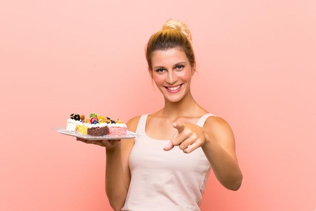 Jovem mulher loira segurando muitos mini bolos diferentes aponta o dedo para você com uma expressão confiante