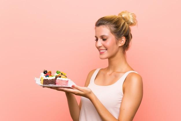 Jovem mulher loira segurando muitos mini bolos diferentes com expressão facial de surpresa