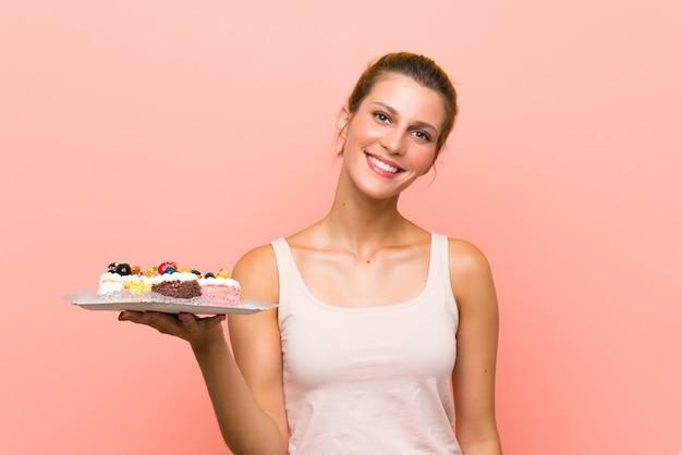 Jovem mulher loira segurando muitos mini bolos diferentes, sorrindo muito