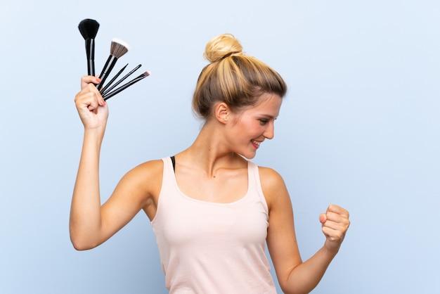Jovem mulher loira segurando muitos pincéis de maquiagem comemorando uma vitória