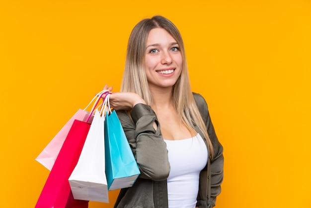 Jovem mulher loira segurando sacolas de compras e sorrindo