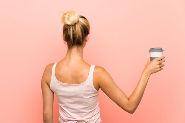Jovem mulher loira segurando um café para viagem em posição traseira