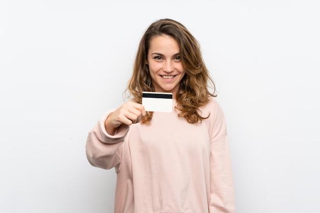 Jovem mulher loira segurando um cartão de crédito