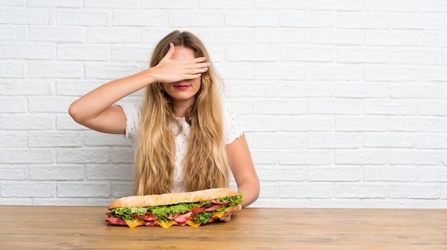 Jovem mulher loira segurando um grande sanduíche cobrindo os olhos