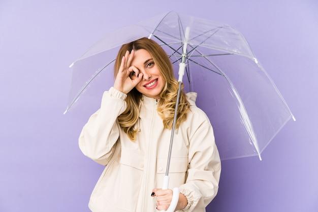 Jovem mulher loira segurando um guarda-chuva isolado jovem mulher loira segurando um guarda-chuva isolado animado mantendo o gesto bem no olho.