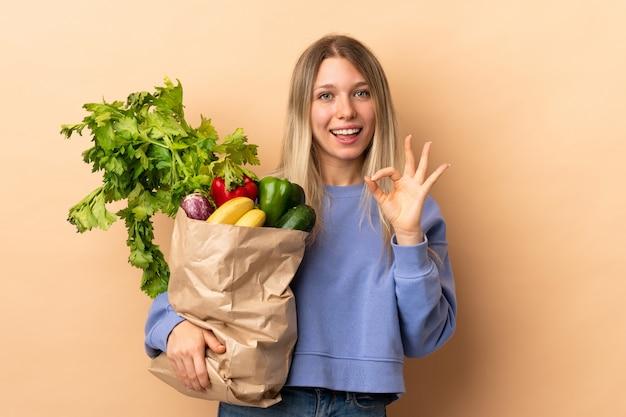 Jovem mulher loira segurando um saco cheio de legumes sobre parede isolada, mostrando um sinal de ok com os dedos