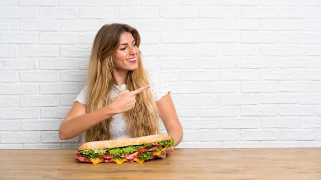 Jovem mulher loira segurando um sanduíche grande, apontando para a lateral
