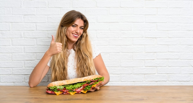 Jovem mulher loira segurando um sanduíche grande com o polegar para cima