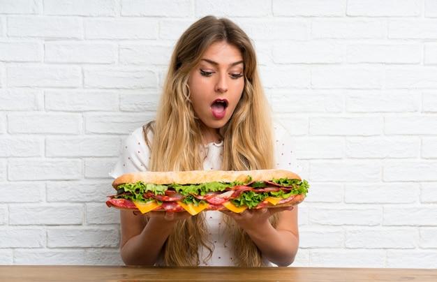 Jovem mulher loira segurando um sanduíche grande, fazendo o gesto de surpresa