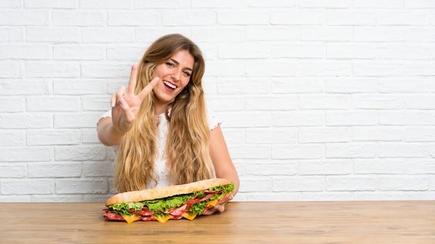 Jovem mulher loira segurando um sanduíche grande, fazendo o gesto de vitória