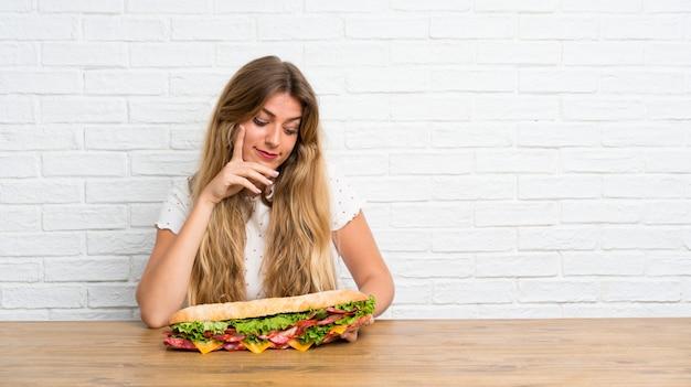 Jovem mulher loira segurando um sanduíche grande