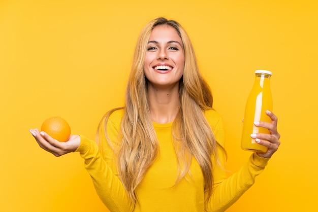 Jovem mulher loira segurando um suco de laranja