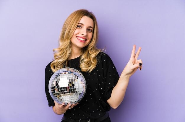 Jovem mulher loira segurando uma bola de festa à noite alegre e despreocupada, mostrando um símbolo de paz com os dedos.