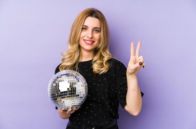 Jovem mulher loira segurando uma bola de festa à noite mostrando o número dois com os dedos.