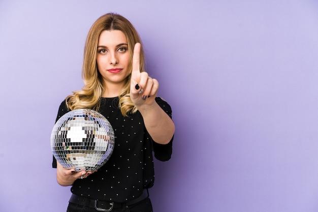 Jovem mulher loira segurando uma bola de festa à noite, mostrando o número um com o dedo.