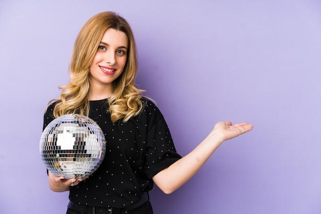 Jovem mulher loira segurando uma bola de festa à noite mostrando um espaço em branco na palma da mão e segurando uma bola de discoteca na outra mão