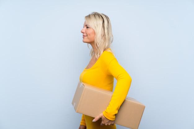 Jovem mulher loira segurando uma caixa para movê-lo para outro site na posição lateral