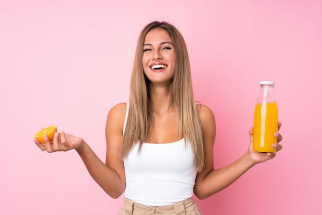 Jovem mulher loira segurando uma laranja