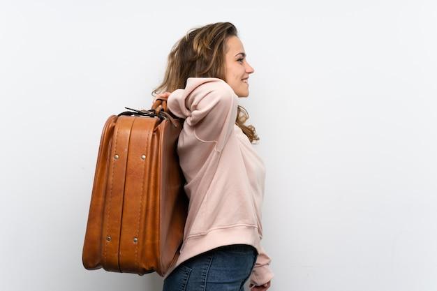 Jovem mulher loira segurando uma mala vintage
