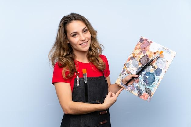Jovem mulher loira segurando uma paleta e apontando-o