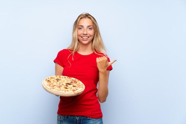 Jovem mulher loira segurando uma pizza sobre parede azul isolada, apontando para o lado para apresentar um produto