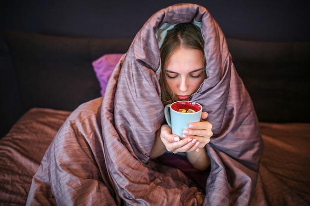 Jovem mulher loira senta-se na cama com a cabeça coberta. ela bebe chá quente da xícara. mulher segura com as duas mãos e olha para baixo.