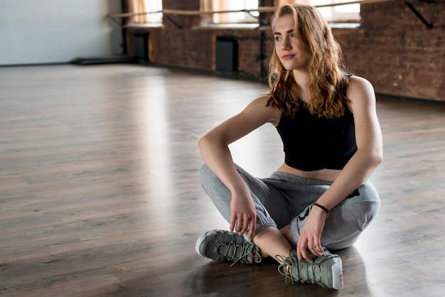 Jovem mulher loira sentada no chão de madeira