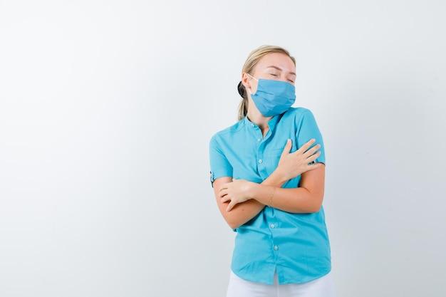 Jovem mulher loira sentindo frio em roupas casuais, máscara e parecendo preocupada
