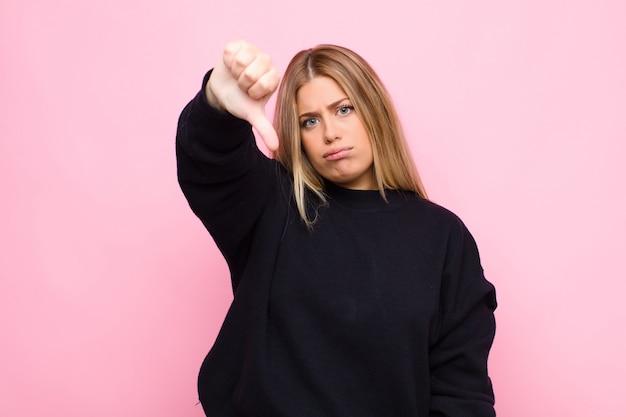 Jovem mulher loira sentindo-se zangado, irritado, irritado, decepcionado ou descontente, mostrando os polegares para baixo com um olhar sério na parede plana