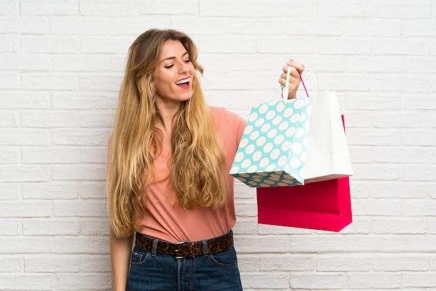 Jovem mulher loira sobre a parede de tijolos brancos, segurando um monte de sacolas de compras